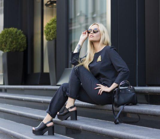 50 modnih savijeta žena ispred hotela u crnom sijedi na stepenicama
